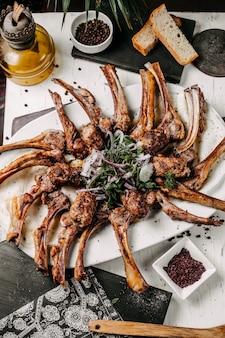 Widok z góry jagnięcy kebab i lula podawane z ziołami z czerwonej cebuli i sumaksem na stole