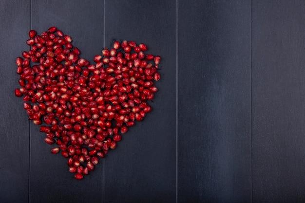 Widok z góry jagód granatu na czarnej powierzchni serca koncepcja