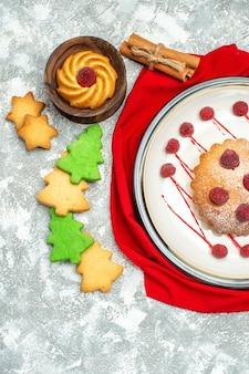 Widok z góry jagodowe ciasto na białym owalnym talerzu czerwony szal ciasteczka xmas drzewa na szarej powierzchni