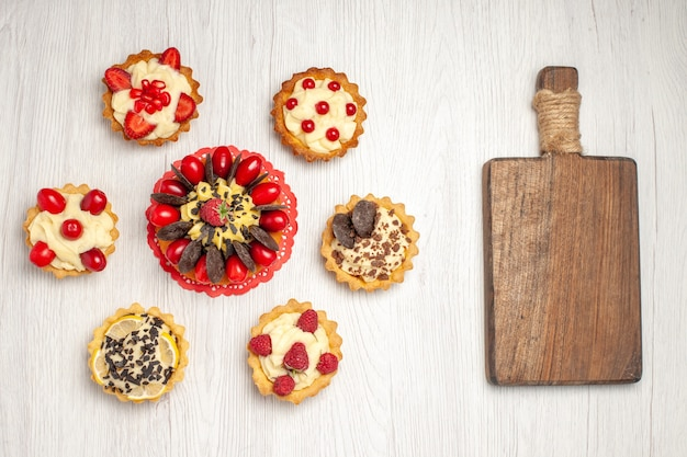 Widok z góry jagodowe ciasto na czerwonych owalnych koronkowych tartach serwetkowych i drewnianej desce do krojenia na białym drewnianym podłożu