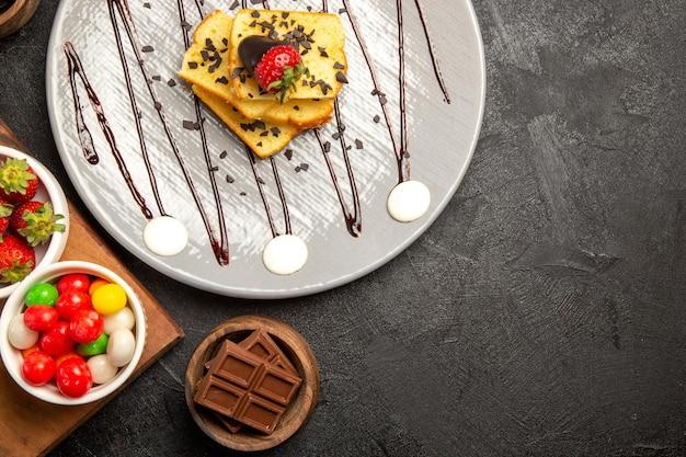 Widok z góry jagody talerz ciasta czekolada i truskawki obok misek czekoladowych słodyczy i truskawek na desce do krojenia
