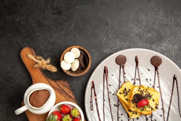 Widok z góry jagody talerz ciasta czekolada i truskawki obok misek z czekoladą i truskawkami na kuchennej desce