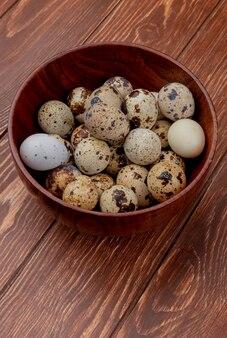 Widok z góry jaj przepiórczych z kremowymi skorupkami na drewnianej misce na drewnianym tle