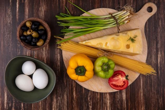 Widok z góry jaja kurze w misce z oliwkami, zieloną cebulą, papryką i plasterek sera maasdam z pomidorami na podłoże drewniane