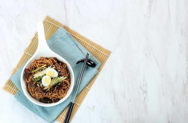 Widok z góry jajangmyeon lub jjajangmyeon to koreański makaron z polewą z czarnego sosu z jajkiem przepiórczym