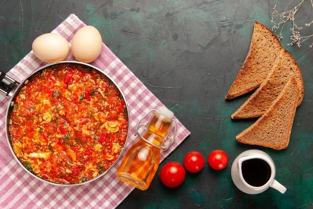 Widok z góry jajecznica z pomidorami i bochenkami chleba na ciemnozielonym tle