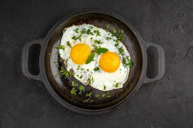 Widok z góry jajecznica z zieleniną wewnątrz patelni na ciemnym tle śniadanie jedzenie posiłek kolor obiad omlet chleb herbata poranna