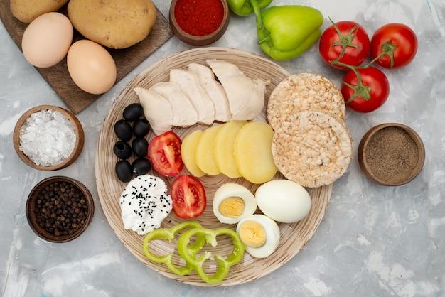 Widok z góry jajka na twardo z oliwkami, papryką, piersiami i pomidorami na szarym, warzywnym posiłku śniadaniowym