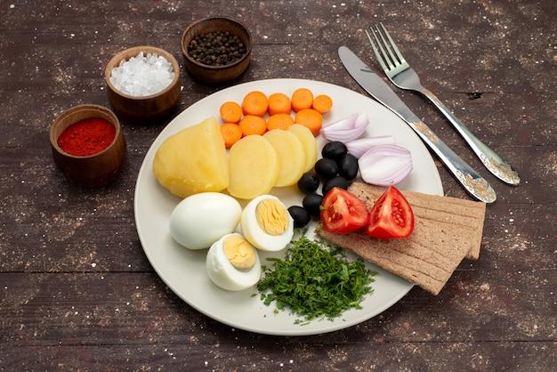 Widok z góry jajka na twardo z oliwkami, zielenią, czosnkiem i pomidorami na brązowym, warzywnym śniadaniu