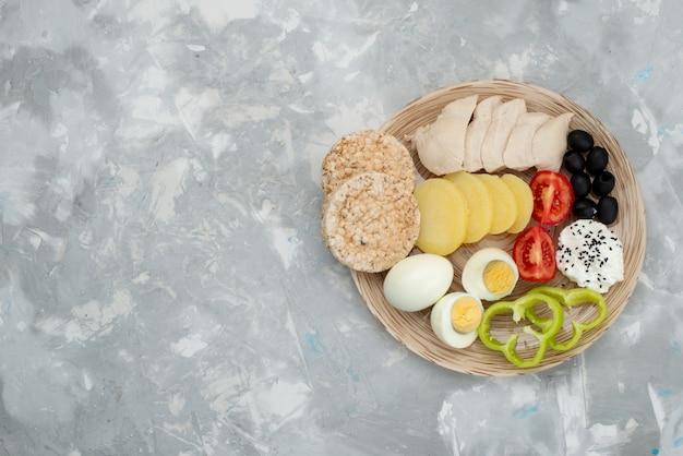 Widok z góry jajka na twardo z piersiami oliwek i pomidorami na szarym, warzywnym śniadaniu
