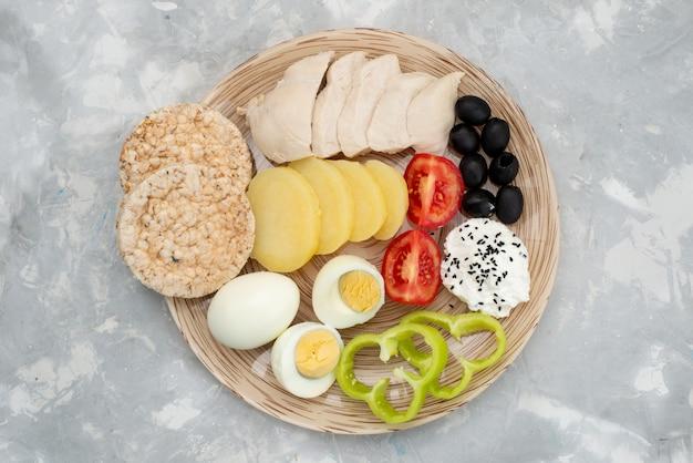 Widok z góry jajka na twardo z przyprawami z piersi oliwek i pomidorami na szarym, warzywnym śniadaniu