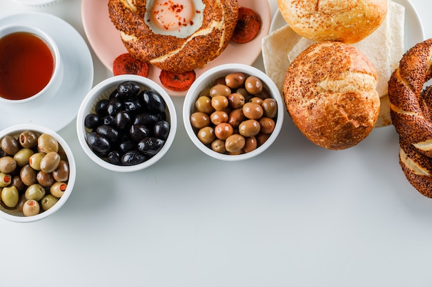 Widok z góry jajka z kiełbasą w talerzu z filiżanką herbaty, turecki bajgiel, oliwka, chleb na białej powierzchni