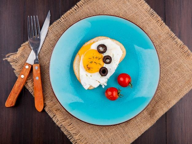 Widok z góry jajko sadzone z pomidorami i oliwkami w talerz i widelec z nożem na worze na drewno
