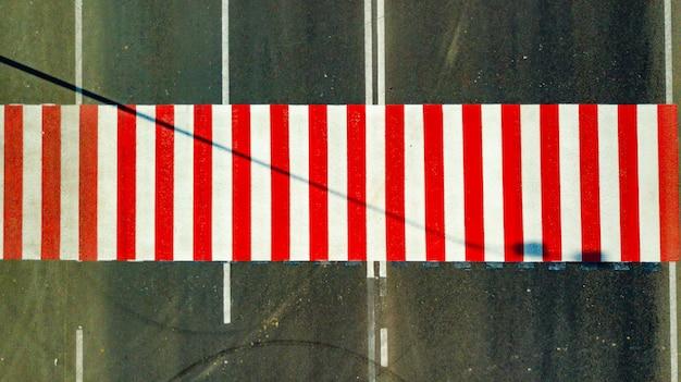 Widok z góry jaskrawo pomalowanych czerwonych i białych pasów na drodze do przechodzenia przez ulicę
