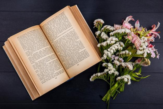 Widok z góry jasnoróżowych kwiatów z otwartą książką na czarnej powierzchni