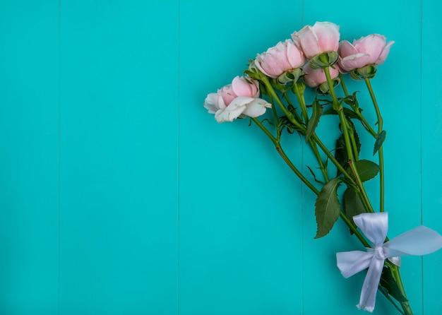 Widok z góry jasnoróżowych róż na jasnoniebieskiej powierzchni