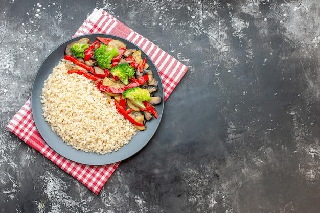 Widok z góry jęczmień perłowy ze smacznymi gotowanymi warzywami na szarym stole ryż dieta kolor olej mączka zdjęcie zdrowe życie wolna przestrzeń