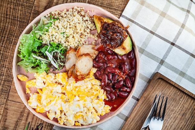 Widok z góry jedzenie leżał płasko. nowoczesna kuchnia tradycyjne angielskie śniadanie z miejsca kopiowania. jedzenie w restauracji. bulgur, zielona sałatka, fasola, awokado, karmelizowana cebula, omlet, kurczak na talerzu. skopiuj miejsce