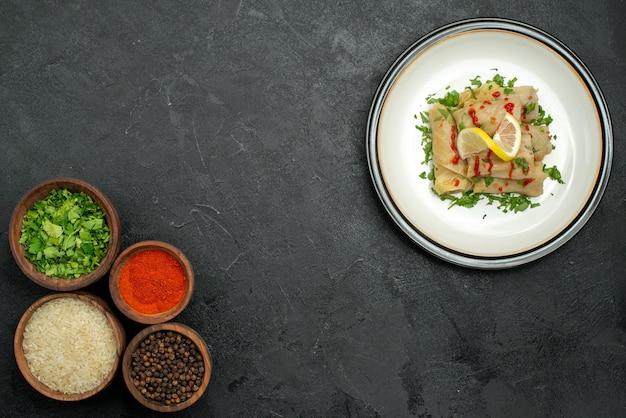 Widok z góry jedzenie na białym talerzu biały talerz gołąbki z sosem ziół i cytryny po prawej stronie oraz miski z przyprawami ryż ziołami i sosem po lewej stronie czarnego stołu