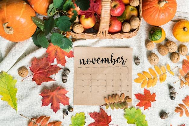 Widok z góry kalendarza listopadowego w otoczeniu czerwonych dojrzałych jabłek, dyni, orzechów włoskich, żołędzi i jesiennych liści