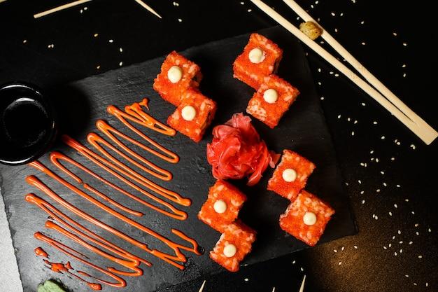 Widok z góry kalifornijskie bułeczki z sosem imbirowym i sojowym na stojaku z pałeczkami