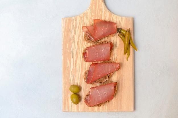 Widok z góry kanapek z pokrojonym suszonym mięsem podawanych na desce do krojenia na neutralnym szarym tle