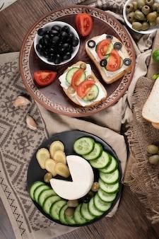 Widok z góry kanapki z oliwek z chlebem i krojonymi ogórkami