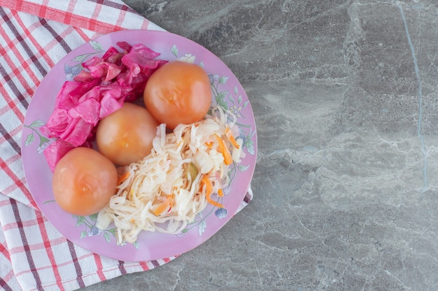 Widok z góry, kapusta kiszona z pomidorem na różowym talerzu.