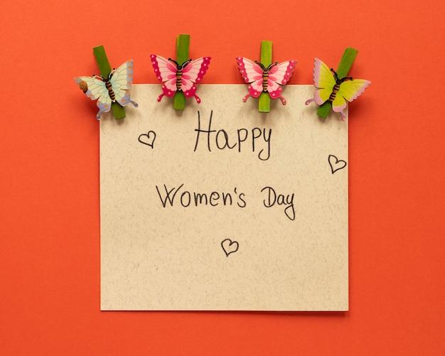 Widok z góry karty z papierowymi motylkami i szpilkami odzieżowymi na dzień kobiet
