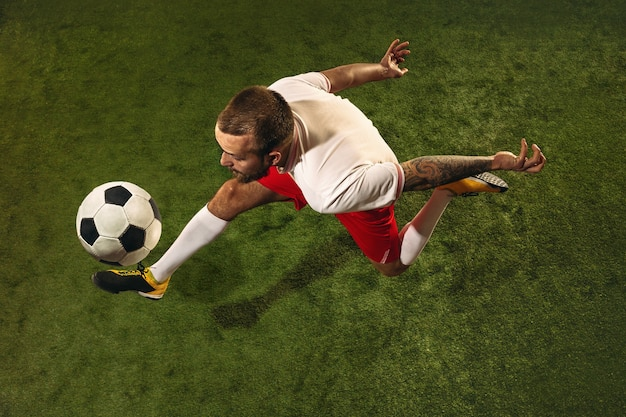 Widok z góry kaukaski piłkarz lub piłkarz na zielonym tle trawy. młody mężczyzna sportowy model szkolenia, ćwiczenia. kopanie piłki, atakowanie, łapanie. pojęcie sportu, rywalizacji, wygrywania.