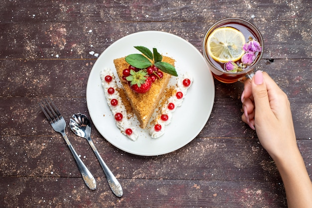 Widok z góry kawałek ciasta miodu z żurawiną wewnątrz białej płytki wraz z herbatą na ciemnym tle ciasto herbata