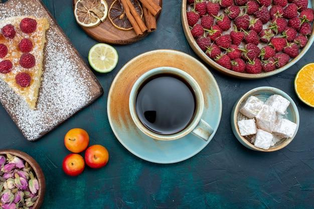 Widok z góry kawałek ciasta pieczony na słodko z malinami i herbatą na ciemnej podłodze ciasto z jagodami i cukrem do pieczenia ciastka