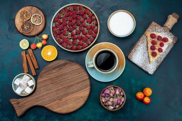 Widok z góry kawałek ciasta pieczony na słodko z malinami i herbatą na ciemnym biurku ciasto jagodowe do pieczenia ciastek