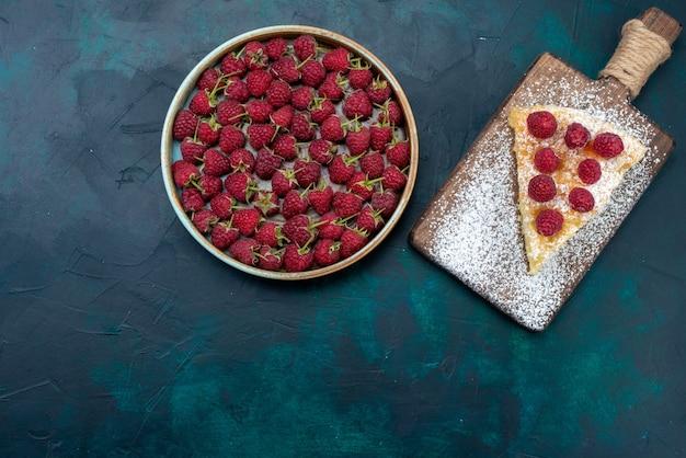Widok z góry kawałek ciasta pieczony na słodko z malinami na ciemnym biurku