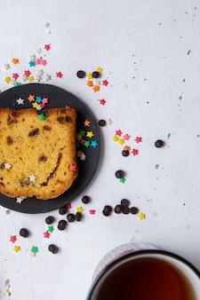 Widok z góry kawałek ciasta wewnątrz ciemnego talerza z kolorowymi cukierkami na jasnym tle ciasto słodkie cukier wypieki