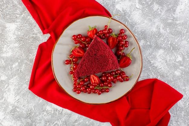 Widok z góry kawałek czerwonego ciasta kawałek ciasta owocowego wewnątrz płyty ze świeżymi żurawinami i truskawkami na szarym biurku ciasto słodka herbata biszkoptowa