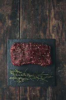 Widok z góry kawałek surowego mięsa na czarnej kamiennej podkładce z rozmarynem, wszystko na postarzanym drewnianym stole