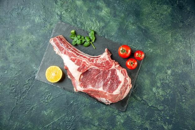 Widok z góry kawałek świeżego mięsa z czerwonymi pomidorami na ciemnoniebieskim tle kuchnia zwierzę krowa jedzenie kolor mięsa rzeźnika