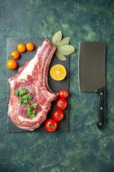 Widok z góry kawałek świeżego mięsa z pomidorami na ciemnoniebieskim tle jedzenie mięso kuchnia zwierzę krowa rzeźnik kurczak kolory