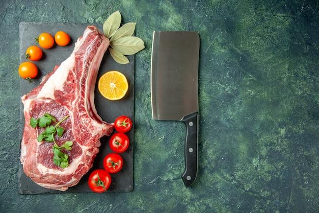 Widok z góry kawałek świeżego mięsa z pomidorami na ciemnoniebieskim tle jedzenie mięso kuchnia zwierzę rzeźnik kurczak kolor krowa