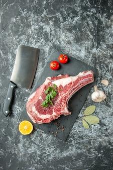 Widok z góry kawałek świeżego mięsa z pomidorami na jasnoszarym tle kuchnia zwierzę krowa kurczak jedzenie kolor mięso rzeźnika