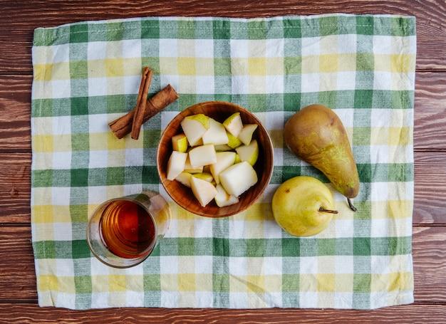 Widok z góry kawałków gruszki w drewnianej misce ze szklanką lemoniady i cynamonu na kraciastym obrusie