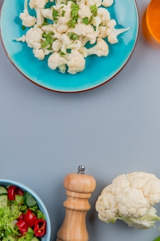 Widok z góry kawałków kalafiora z kolendrą w talerzu masła i sałatki warzywnej na niebieskim tle