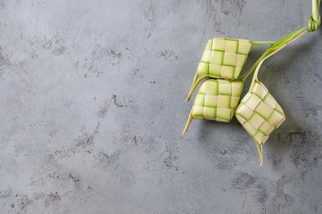 Widok z góry ketupat na białym tle na niedokończonej szarej ścianie. typowe danie z ryżu zawiniętego w papierki z plecionych młodych liści kokosa.