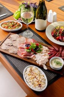 Widok z góry kiełbaski na biurku z białym winem i warzywami na stole posiłek restauracji mięsa