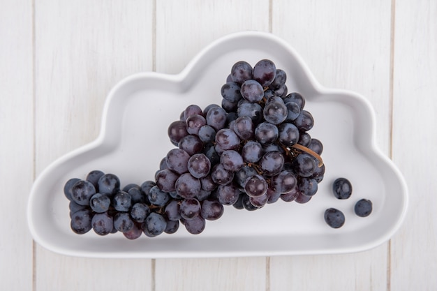 Widok z góry kiść czarnych winogron na płytce w kształcie chmury na białym tle