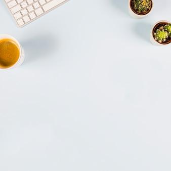 Widok z góry klawiatury; filiżanka kawy i kaktus roślina na białym tle