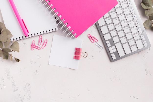 Widok z góry klawiatury na biurku z notatnikami i suszonymi liśćmi