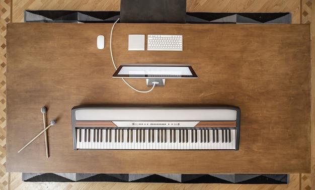 Widok z góry klawiszy muzycznych i komputera na dużym drewnianym stole. miejsce pracy muzyka, minimalizm muzyczny.