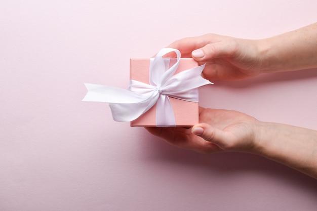 Widok z góry kobieca ręka trzyma różowe pudełko z białą kokardką na różowym tle. miejsce do kopiowania.